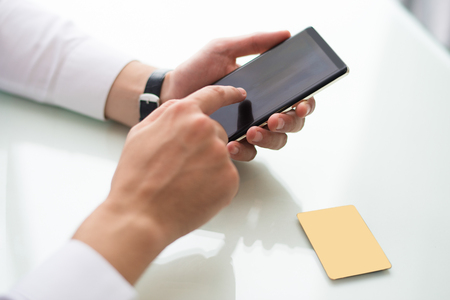 Close-up of unrecognizable man browsing internet on smartphone while searching for information. Businessman sitting at table with credit card and using online payment. Banking concept