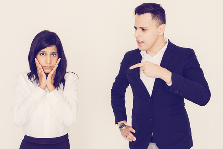 Portrait of angry young North American executive scolding or firing his Indian female employee. Woman standing in stress. Business relationships, racial and sex discrimination concept Banco de Imagens