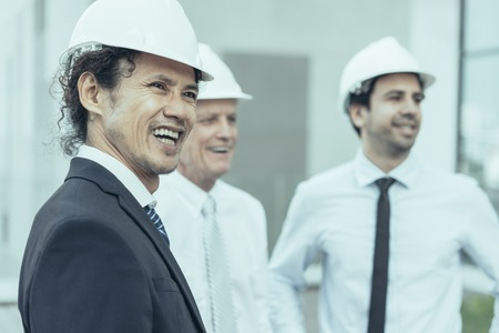 Closeup of three happy diverse business people looking away, wearing helmets and standing outdoors with building in background. Two men in background are blurred. Architects concept. Stock Photo