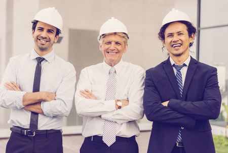 Closeup of three smiling diverse business people looking at camera, wearing helmets and standing with their arms crossed outdoors with building in background. Architects concept. Front view.