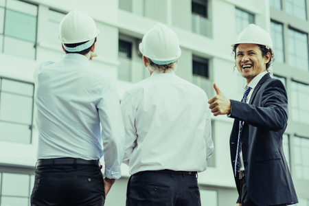 Closeup portrait of three diverse business people wearing helmets and standing outdoors with building in background. One man is showing thumb up. Construction supervising concept. Back view.