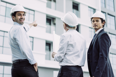 Closeup portrait of three diverse business people wearing helmets, looking at camera and standing outdoors with building in background. Construction supervising concept. Back view.