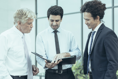 Closeup of three smiling diverse business people discussing issues, looking through document in folder and standing outdoors with building in background. Business issues concept. Stock Photo