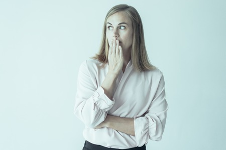 Portrait of young Caucasian woman wearing pink blouse covering mouth afraid to say a word or keeping secret. Secrecy concept