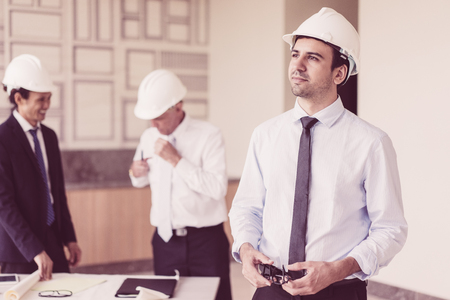 Portrait of young pensive man in helmet and tie with two talking colleagues in blurred background. Young architect looking at neighboring building out of window. Meeting and building concept Banco de Imagens