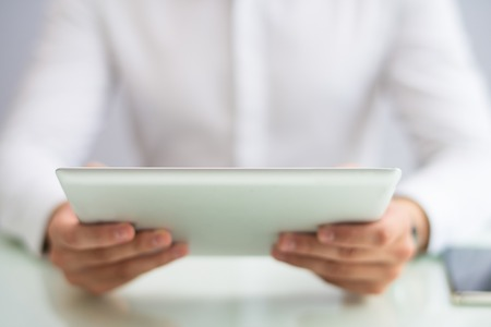 Closeup of person holding tablet computer. Man browsing on digital device. Technology and communication concept. Cropped view.