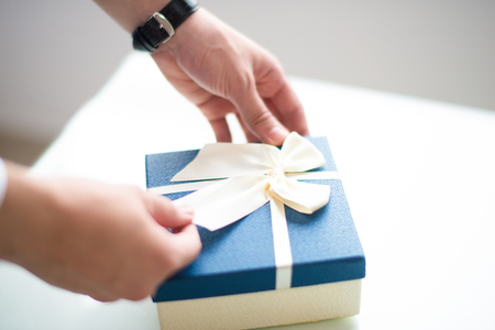 Closeup of person tying bow on gift box. Man wrapping gift. Gift concept. Cropped view.