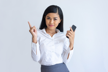 Content Asian girl with phone having idea. Young woman holding smartphone and pointing index finger at copy space upward. Communication and promotion concept