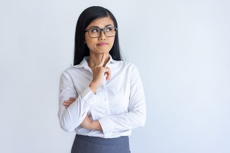 Pensive Chinese office girl studying new information. Young Asian woman in glasses and white shirt looking at copy space away. Thinking and advertising concept Stockfoto
