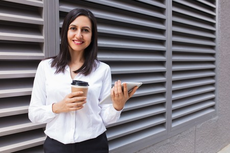 Portrait of smiling young businesswoman with coffee and touchpad. Caucasian woman using digital tablet at coffee break outdoors. Coffee break concept 免版税图像