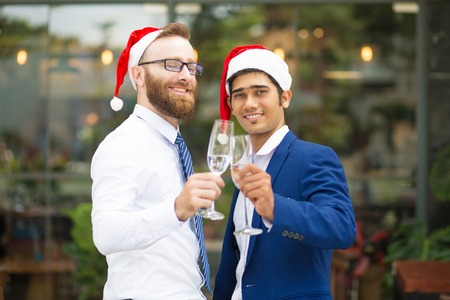 Happy excited multi-ethnic men clinking champagne flutes and looking at camera. Cheerful optimistic managers in formalwear celebrating Christmas. Office party concept