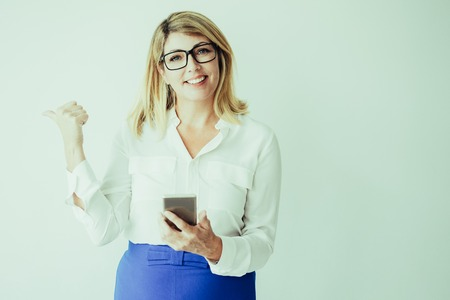 Closeup portrait of smiling attractive fair-haired woman looking at camera, pointing thumb backwards and holding smartphone. Technology promotion concept. Isolated front view on grey background.