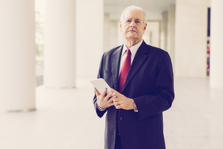 Closeup portrait of serious senior business man looking at camera and using tablet computer in office hall. Successful senior business man concept. Front view. Reklamní fotografie