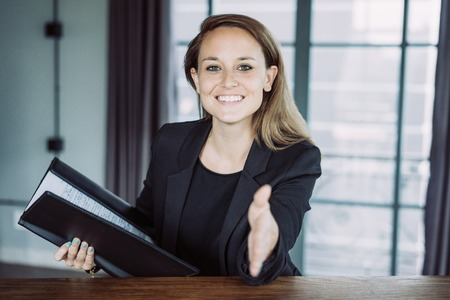 Closeup portrait of smiling young beautiful brown-haired woman looking at camera, extending arm for handshake and holding open folder at desk in hotel lobby. Agreement concept. Front view.