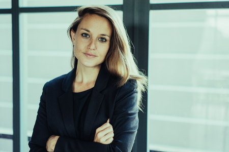 Closeup portrait of confident young beautiful brown-haired business woman looking at camera and standing at window with her arms crossed. Business woman portrait concept. Front view.