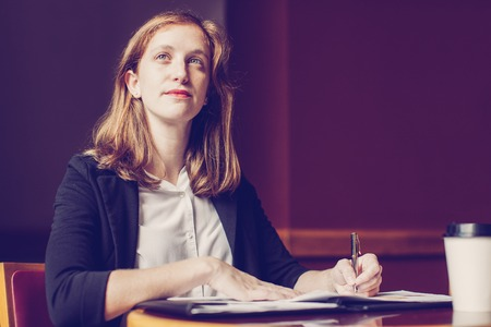 Portrait of concentrated young Caucasian businesswoman sitting at table and working in cafe or office or listening to seminar. Self-employed person and training concept
