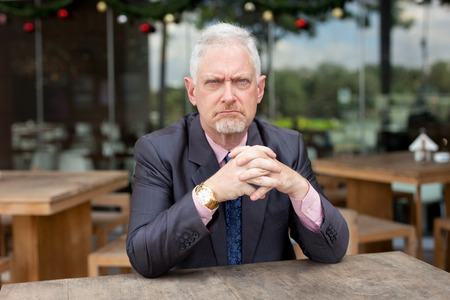 Displeased frowning senior businessman sitting at table in outdoor cafe. Angry bearded man scowling and looking at camera. Sullen concept Stock Photo