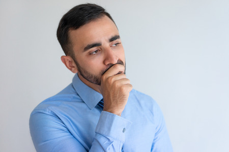 Pensive young bearded man concentrated on thoughts looking into distance. Contemplative businessman touching chin while brainstorming. Idea concept Stockfoto