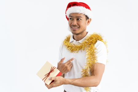 Happy Asian man receiving gift box and pointing at himself. Guy wearing Santa hat, tinsel and looking away. Christmas gift concept. Isolated view on white background.