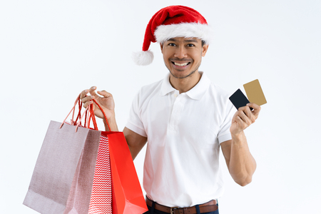 Man wearing Santa hat, holding credit cards and shopping bags. Isolated front view on white background. Stock Photo