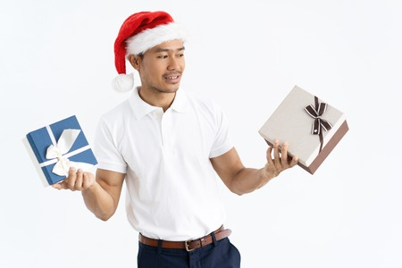 Pensive man wearing Santa hat and holding two gift boxes. Isolated front view on white background. Archivio Fotografico