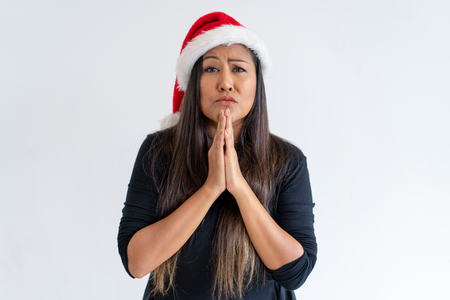 Worried Christmas lady begging for help. Nervous mix raced woman in Santa hat keeping hands together in praying gesture. Praying concept Zdjęcie Seryjne
