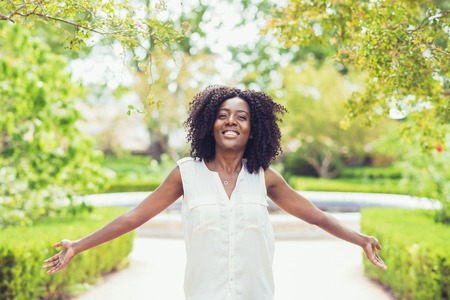 Happy pretty black woman spreading hands in park with summer plants in background. Park relaxation and happiness concept. Front view. Banque d'images