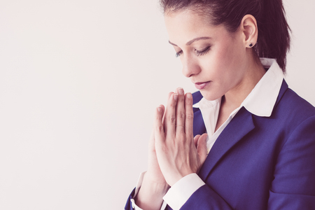 Closeup of calm young Caucasian woman putting hands together in praying. Businesswoman in formal suit meditating with closed eyes. Business and praying concept