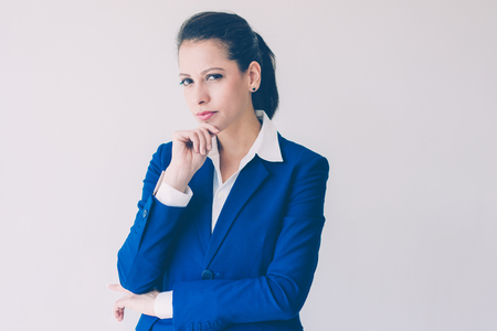 Portrait of serious young Caucasian woman in blue formal suit. Frowning businesswoman with suspicious face leaning chin on hand. Business and corporate portrait concept