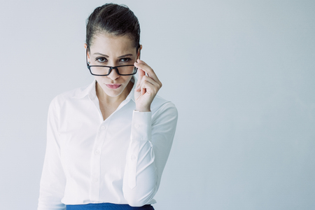 Suspicious arrogant young businesswoman looking over her glasses. Confident Caucasian female business specialist with contemptuous glance looking at camera. Entrepreneur concept