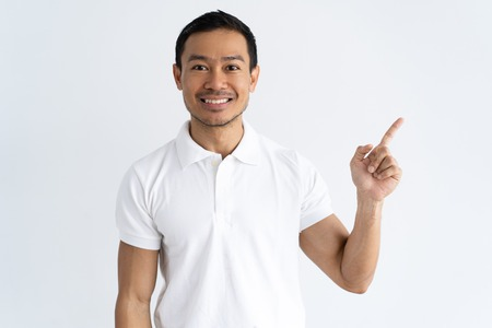 Cheerful young man sharing important news. Smiling guy dressed in white polo pointing finger at copy space away. Presentation concept