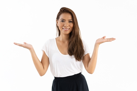 Joyful mix raced girl presenting information. Beautiful young woman pointing hands at both sides. Advertising concept