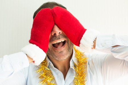 Cheerful excited man in Santa mittens covering eyes while waiting for Christmas. Happy businessman with tinsel in anticipation of holidays. Christmas joy concept