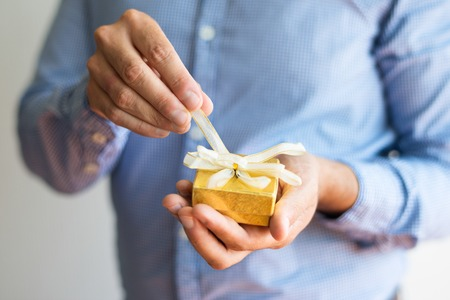 Close-up of man untying bow on small yellow box. Unrecognizable man opening Christmas gift. Birthday gift concept Stock Photo