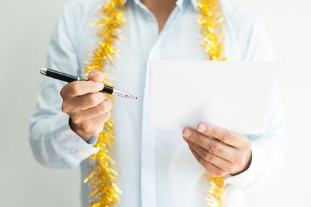 Close-up of man with tinsel around neck signing letter. Unrecognizable businessman examining letter. Composing Christmas letter concept Reklamní fotografie