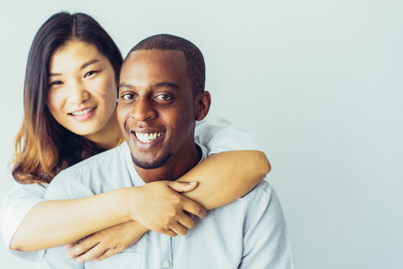 Happy Asian woman embracing handsome African guy and looking at camera. Positive excited beautiful multiethnic couple happy together. Relationship and love concept 版權商用圖片