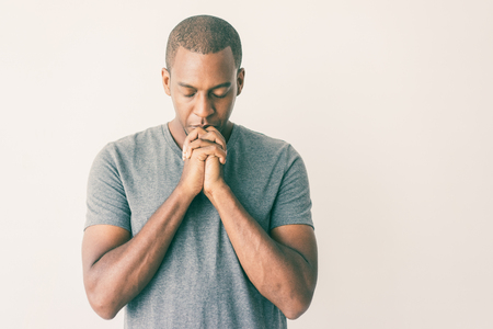 Calm spiritual handsome African guy praying with closed eyes. Serious peaceful young man with joining hands meditating. Belief concept Stok Fotoğraf