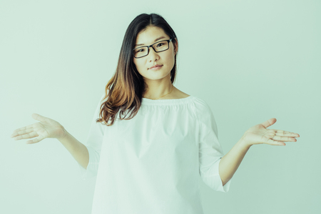Puzzled Chinese student girl shrugging shoulders and looking at camera. Misunderstanding beautiful Chinese woman in loose shirt gesturing. Incomprehension concept Stockfoto