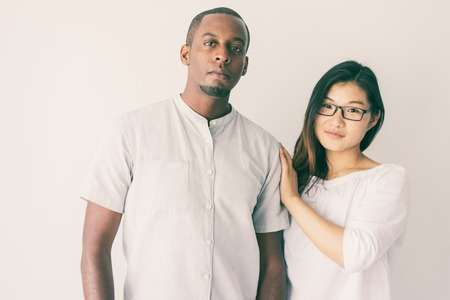 Serious confident young multiethnic couple in casual clothing looking at camera. Pretty Asian lady touching boyfriends shoulder. Interracial couple concept