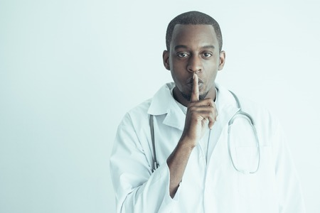 Serious black male doctor showing silence gesture. Medical secrecy concept. Isolated front view on white background. Stock Photo