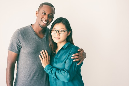 Young Afro American man hugging his Asian girlfriend with glasses. Romantic portrait of interracial couple of students. Love and romance concept