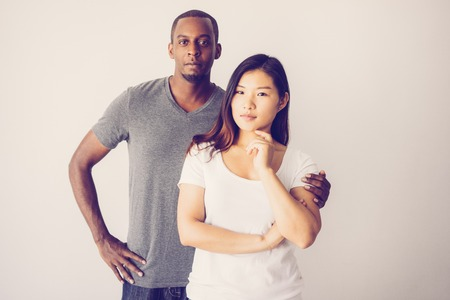 Portrait of young mixed raced couple posing at camera. Confident African American man hugging his Asian girlfriend, girl touching chin. Love and multiracial couple concept