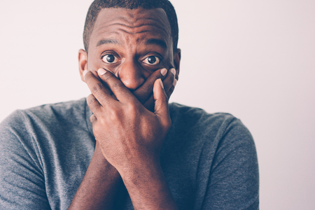 Closeup of shocked African American keeping silence. Frightened black man in grey tshirt covering mouth with hands. Shock and keeping secret concept