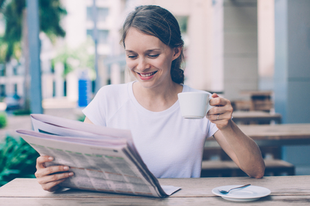 Young woman drinking coffee and reading newspaper at cafe. Portrait of Caucasian girl wearing white T-shirt sitting at table and looking for job ads. Leisure and news concept 版權商用圖片