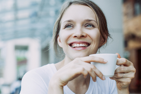 Close-up of young Caucasian woman drinking coffee at street cafe. Smiling face of girl wearing white T-shirt with coffee cup. Coffee break concept