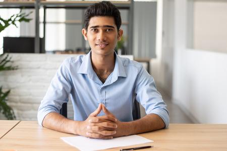 Porträt des glücklichen indischen Managers, der am Tisch mit Papier witzelt. Junger Kandidat, der beim Vorstellungsgespräch im Büro sitzt. Beschäftigungskonzept