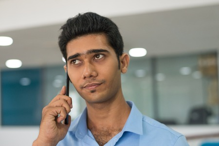 Pensive handsome man listening to customer on mobile phone. Concentrated businessman talking on phone in modern office. Conversation concept