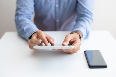 Closeup of man working and tapping on tablet computer. Business man using digital devices. Technology and communication concept. Cropped front view. Stock fotó