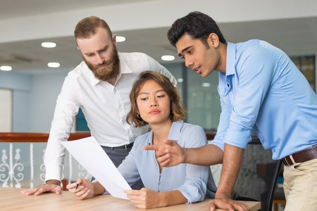 Business colleagues helping newcomer to complete job application form. Young office employee having troubles with document and consulting coworkers. Mentorship or consulting concept