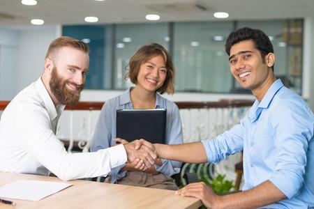 Fröhlicher indischer Kandidat, der glücklich ist, einen Job in einem multinationalen Unternehmen zu bekommen. Glückliche multiethnische Geschäftspartner, die Hände schütteln, junger Assistent, der im Hintergrund lächelt. Berufseinstieg oder Handelskonzept